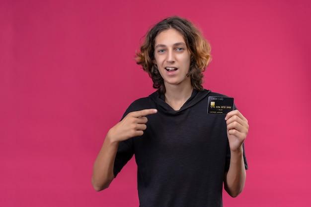 銀行カードを保持し、ピンクの壁にカードを指す黒いtシャツの長い髪の笑顔の男