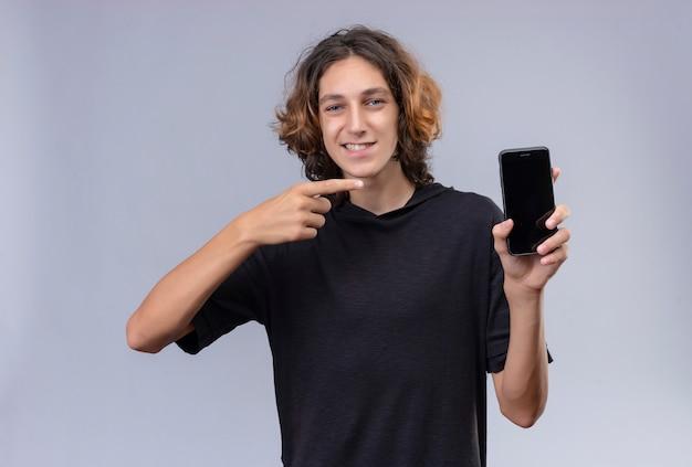 전화를 들고 흰 벽에 전화를 가리키는 검은 티셔츠에 긴 머리를 가진 웃는 남자