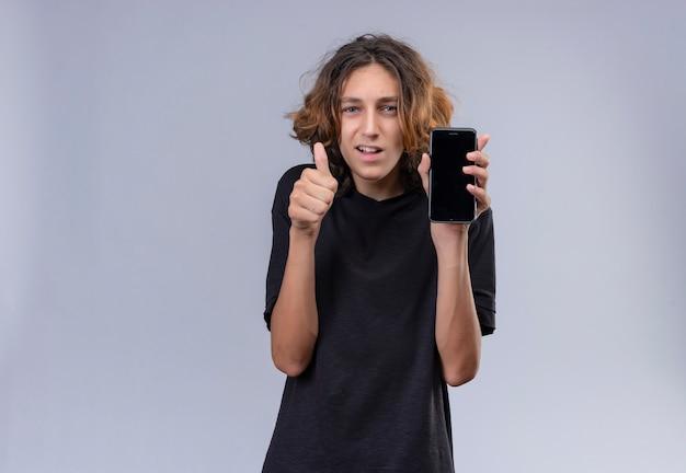 흰 벽에 전화와 엄지 손가락을 들고 검은 티셔츠에 긴 머리를 가진 웃는 남자