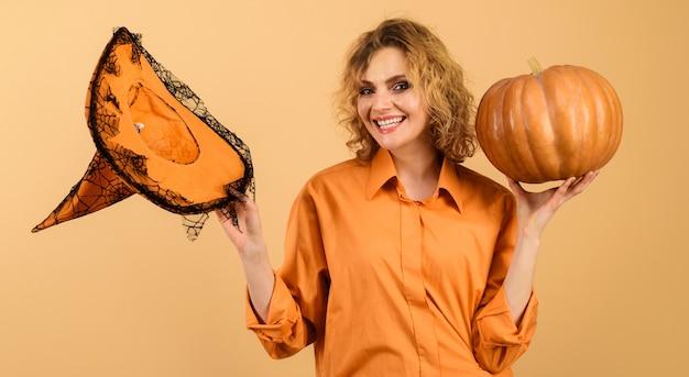 Smiling halloween witch with pumpkin. happy girl with magic witches hat. trick or treat. halloween time.