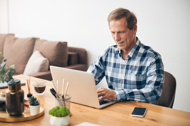 Smiling handsome adult man expressing positivity while reading messages on laptop at home
