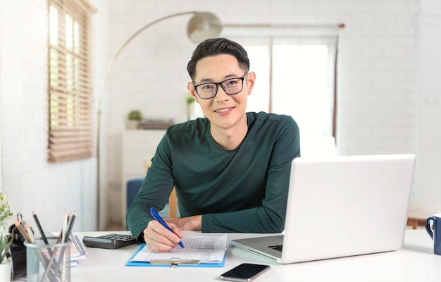 Smiling handsome asian businessman working from home.
