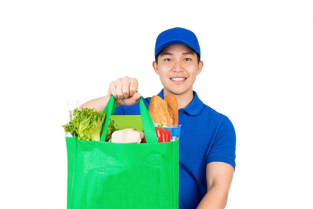 Smiling handsome asian delivery man holding grocery shopping bag giving to customer isolated on white