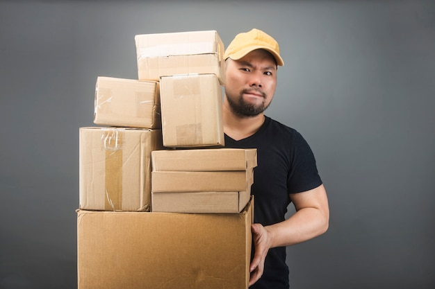Smiling handsome asian delivery man wearing cap, giving and carrying parcel, cardboard box, moving house day and express delivery concept