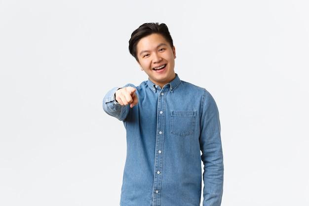中かっこでハンサムなアジア人の男を笑顔で選択し、カメラに指を向け、何かを選択または選択し、人を見つけ、白い背景に立って、あなたを祝福します。