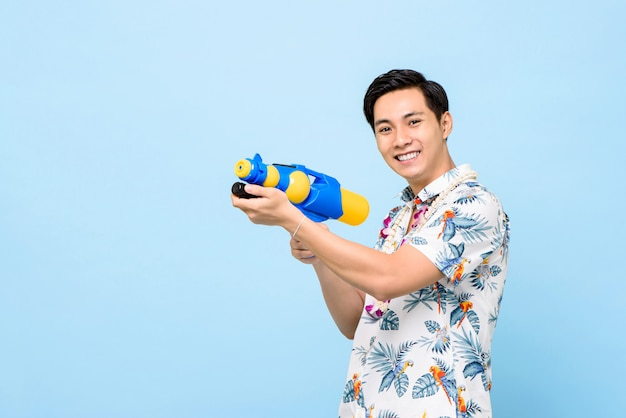 Smiling handsome asian man playing with water gun during songkran festival in thailand and southeast asia