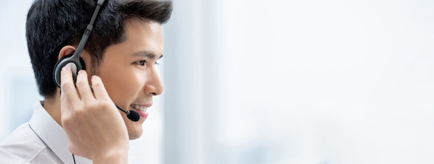 Усмехаясь наушники красивого азиатского человека нося работая в центре телефонного обслуживания как оператор обслуживания клиента