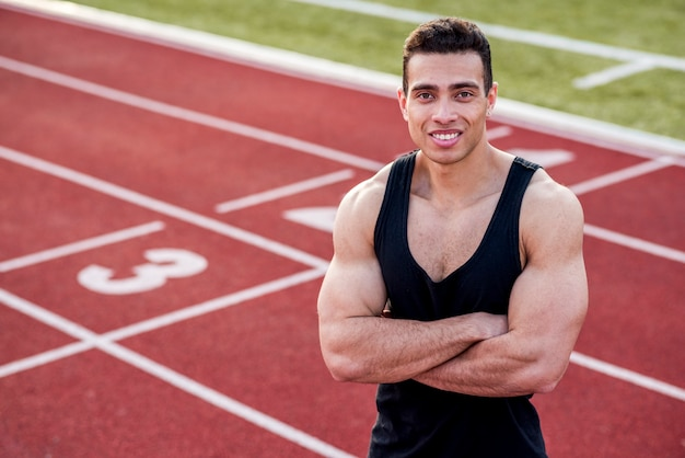 Smiling handsome athlete in a sporty outfit with his arms crossed on race track looking at camera