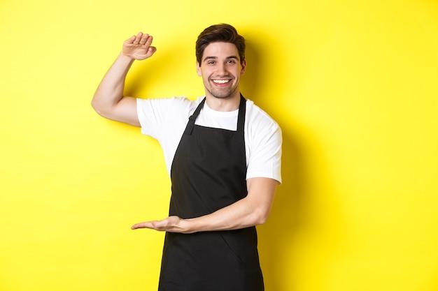 Улыбающийся красивый бариста показывает что-то длинное или большое, стоя на желтом фоне.