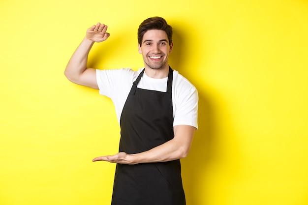 Улыбающийся красивый бариста показывает что-то длинное или большое, стоя над желтой стеной