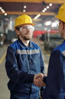 공장에서 동료와 악수하는 안전모와 고글을 쓴 잘생긴 수염 난 백인 직원