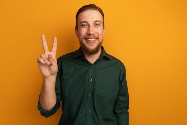 오렌지 벽에 고립 된 잘 생긴 금발 남자 제스처 승리 손 기호 미소