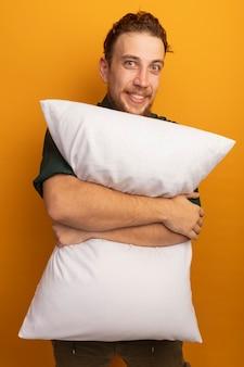 L'uomo biondo bello sorridente tiene il cuscino isolato sulla parete arancione