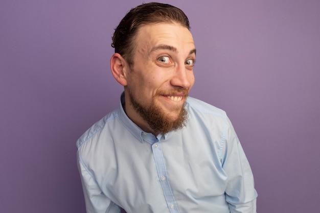 Uomo biondo bello sorridente che esamina fronte isolato sulla parete viola