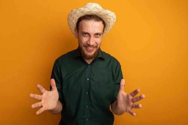 ビーチ帽子と笑顔のハンサムなブロンドの男は、オレンジ色の壁で隔離の手を開いた