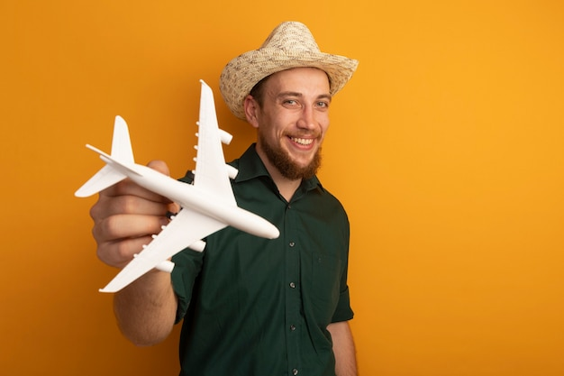 Smiling handsome blonde man with beach hat holds model plane on orange