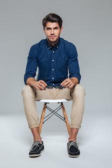 Улыбающийся красивый брюнет в синей рубашке сидит на стуле и держит солнцезащитные очки