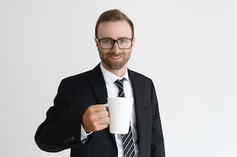 Smiling handsome business man holding mug, drinking tea and looking at camera.