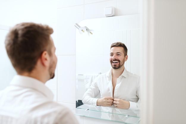 鏡の前のバスルームに立っている間仕事のために服を着せる笑顔のハンサムな実業家。