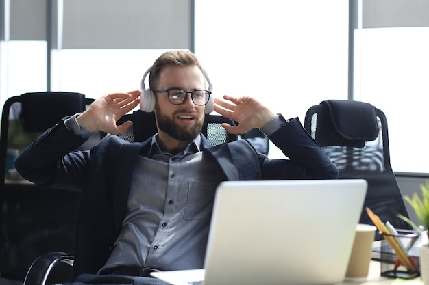 Smiling handsome businessman relaxing and listening music in earphones in a modern office.