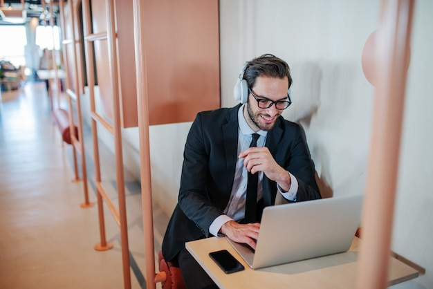 眼鏡とヘッドフォンが職場で座っているとラップトップを使用して、スーツでハンサムな白人ひげを生やした実業家の笑みを浮かべてください。