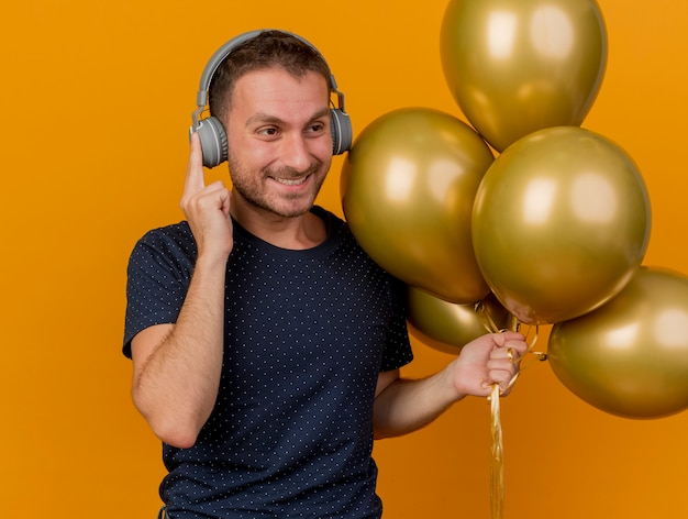 헤드폰에 웃는 잘 생긴 백인 남자는 복사 공간 오렌지 배경에 고립 된 측면에서 찾고 헬륨 풍선을 보유하고