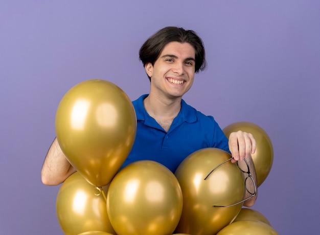 光学ガラスを保持しているヘリウム風船で立っているハンサムな白人男性の笑みを浮かべてください。