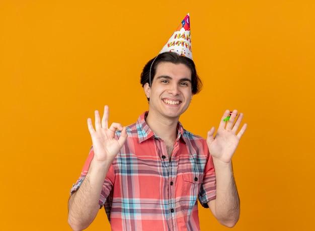 생일 모자를 쓰고 웃는 잘 생긴 백인 남자가 확인 손 기호를 몸짓으로하고 파티 휘파람을 보유하고 있습니다.