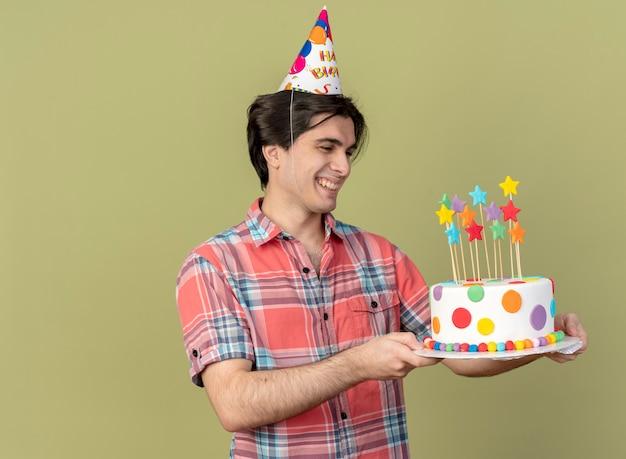 誕生日の帽子をかぶった笑顔のハンサムな白人男性が誕生日ケーキを手に持って見る