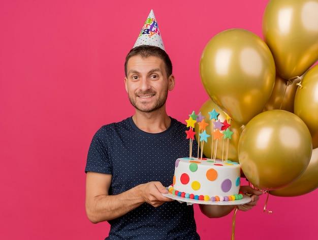 バースデーキャップを身に着けているハンサムな白人男性の笑顔は、コピースペースでピンクの背景に分離されたバースデーケーキとヘリウム風船を保持します。