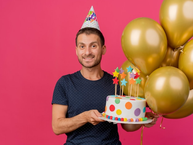 Smiling handsome caucasian man wearing birthday cap holds birthday cake and helium balloons isolated on pink background with copy space