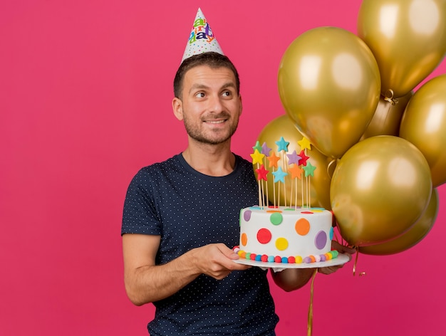Smiling handsome caucasian man wearing birthday cap holds birthday cake and helium balloons looking at side isolated on pink background with copy space