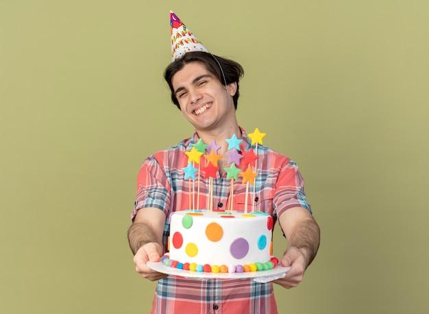 誕生日の帽子をかぶった笑顔のハンサムな白人男性がバースデー ケーキを持っている