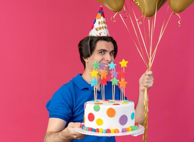 Smiling handsome caucasian man wearing birthday cap holds helium balloons and birthday cake