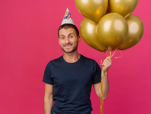 誕生日の帽子をかぶって笑顔のハンサムな白人男性は、コピースペースでピンクの背景に分離されたヘリウム風船を保持します。
