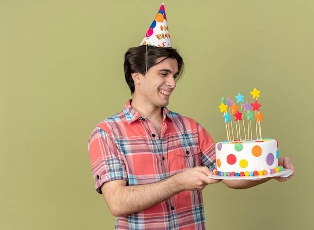 Smiling handsome caucasian man wearing birthday cap holds and looks at birthday cake