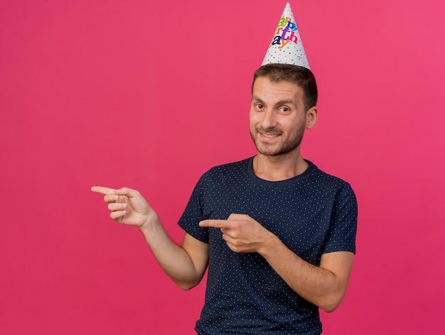 コピースペースとピンクの背景に分離された両手で横を指している誕生日の帽子をかぶってハンサムな白人男性の笑顔