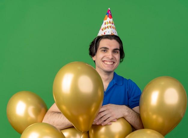 Улыбающийся красивый кавказский мужчина в шапочке на день рождения стоит с гелиевыми шарами