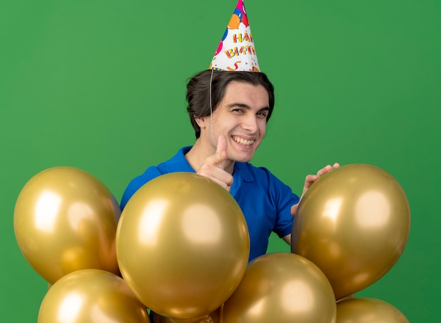 Smiling handsome caucasian man wearing birthday cap stands with helium balloons pointing at camera