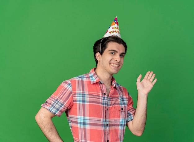 誕生日の帽子をかぶった笑顔のハンサムな白人男性が手を挙げて立つ