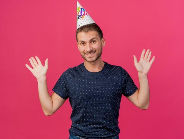 コピースペースとピンクの背景に分離された上げられた手で誕生日キャップを身に着けているハンサムな白人男性の笑顔