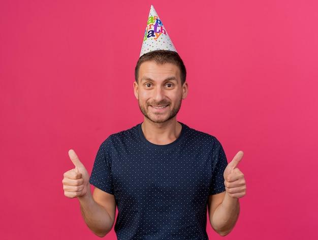 コピースペースでピンクの背景に分離されたカメラを見て両手で親指を立てて誕生日の帽子をかぶったハンサムな白人男性