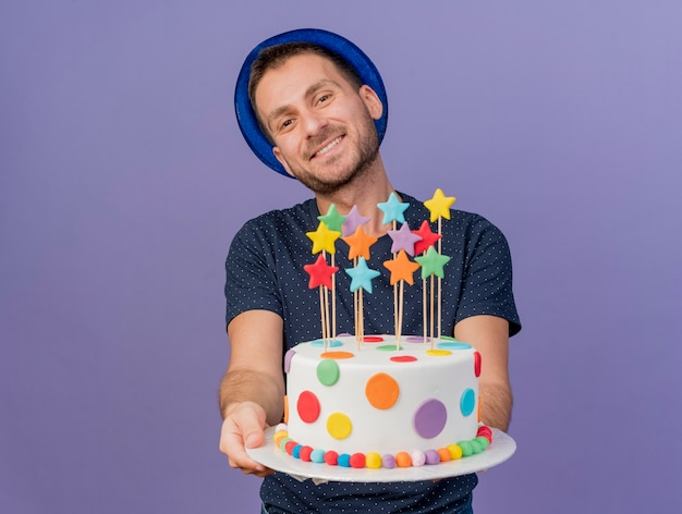 Smiling handsome caucasian man wearing blue hat holds birthday cake looking at camera isolated on purple background with copy space Free Photo