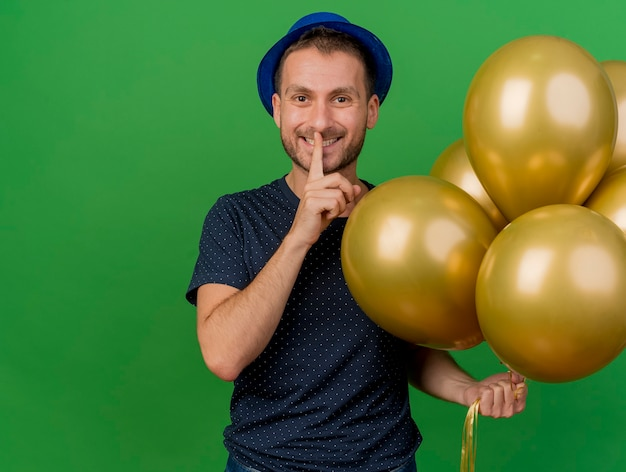 Smiling handsome caucasian man wearing blue party hat gestures silence and holds helium balloons isolated on green background with copy space