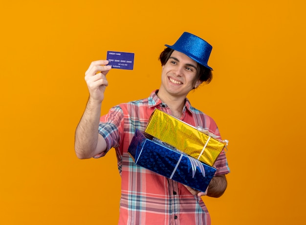 Smiling handsome caucasian man wearing blue party hat holds gift boxes and looks at credit card