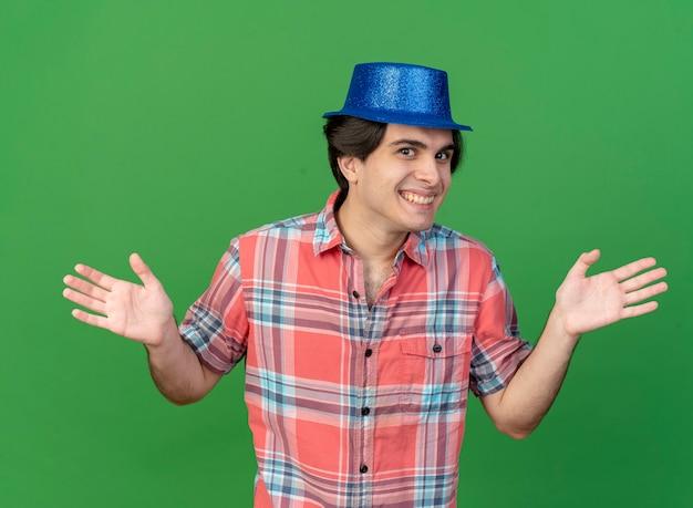 Un bell'uomo caucasico sorridente che indossa un cappello da festa blu tiene le mani aperte
