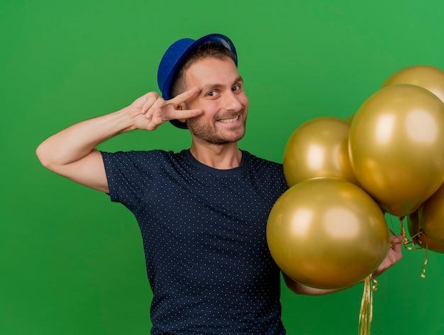 青いパーティーハットを身に着けているハンサムな白人男性の笑顔は、ヘリウム気球を保持し、コピースペースで緑の背景に分離された勝利の手サインをジェスチャーします。