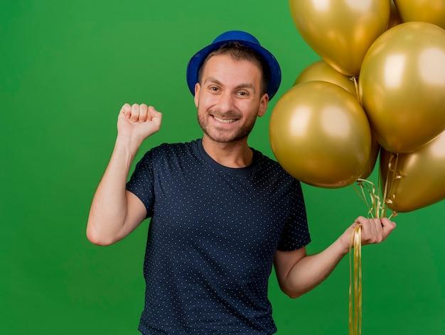 블루 파티 모자를 쓰고 웃는 잘 생긴 백인 남자는 헬륨 풍선을 보유하고 복사 공간이 녹색 배경에 고립 된 주먹을 유지
