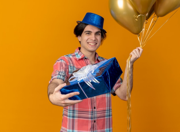 Smiling handsome caucasian man wearing blue party hat holds helium balloons and gift box