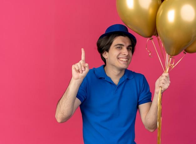 블루 파티 모자를 쓰고 웃는 잘 생긴 백인 남자가 가리키는 헬륨 풍선을 보유